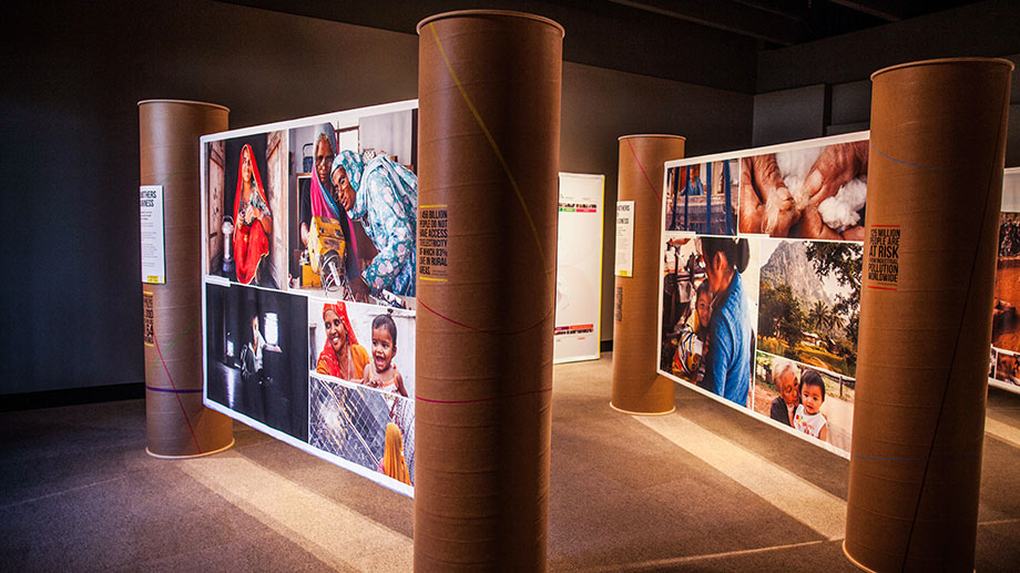 Photo stories on textile panels suspended between cardboard pillars.